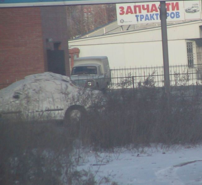 car covered with snow driving across streets of Russia 2