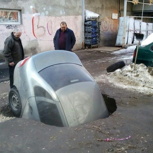 Car With a Passenger Swallowed By a Sink Hole