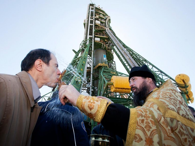 An Orthodox priest blesses a specialist in front of the Soyuz TMA-21 spacecraft at Baikonur cosmodrome