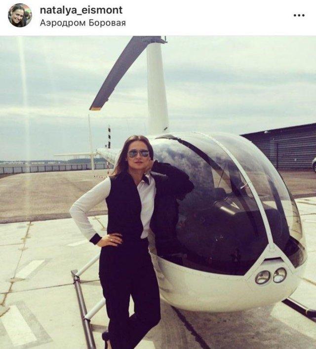 Наталья эйсмонт в белой рубашке и черном костюме на фоне белого вертолета
