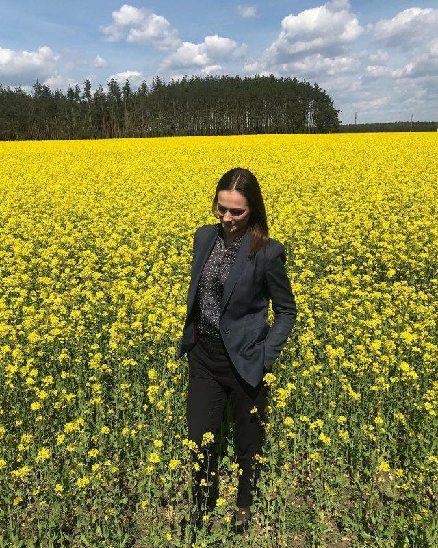 Наталья Эйсмонт в зеленом пиджаке и темных брюках в поле из желтых цветов