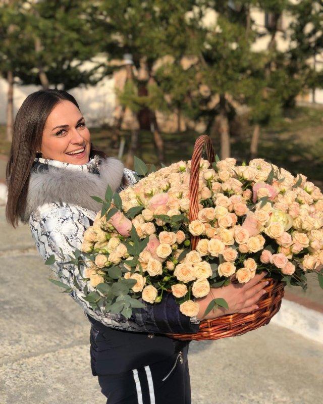 Наталья Эйсмонт в корзиной роз в белом пуховике на улице
